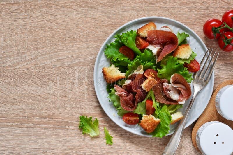 Insalata con il prosciutto di Parma, pomodori ciliegia, patatine fritte del pane sul tavolo da cucina Vista da sopra immagine stock