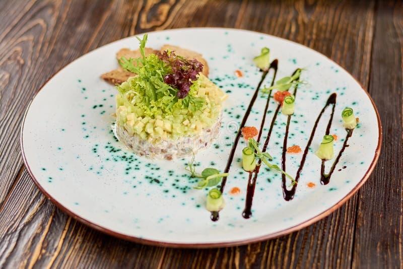 Insalata con l'aringa, l'avocado ed i pani tostati immagini stock libere da diritti