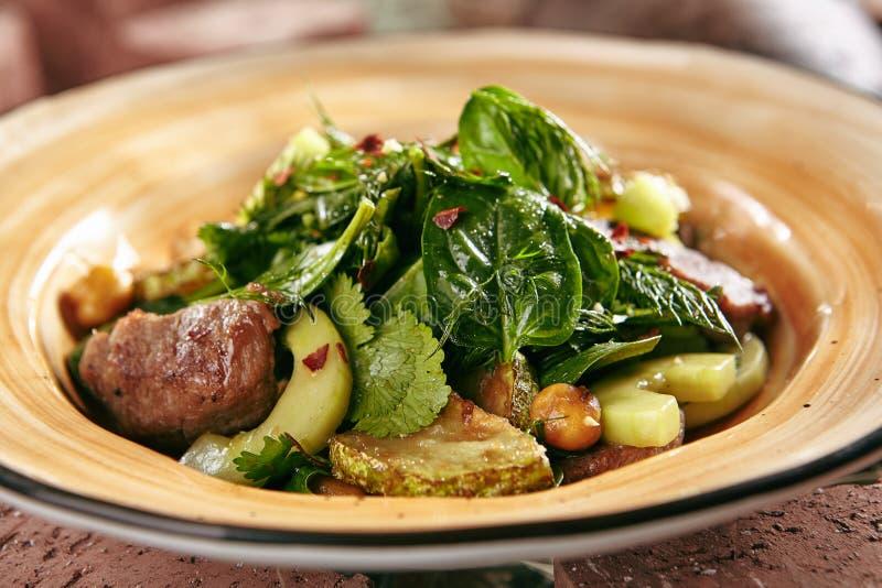 Insalata con la carne e lo zucchini dell'agnello su stile rustico Hay Background immagine stock