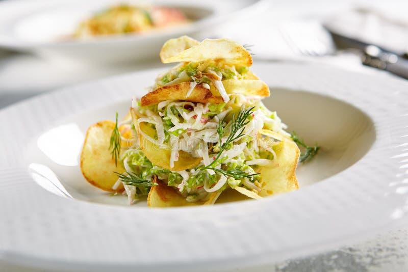 Insalata con le patatine fritte croccanti e le verdure tagliate delle strisce immagini stock