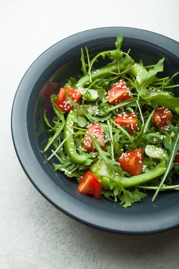 Insalata degli ortaggi freschi e delle erbe in un piatto su un fondo bianco, vista superiore fotografia stock