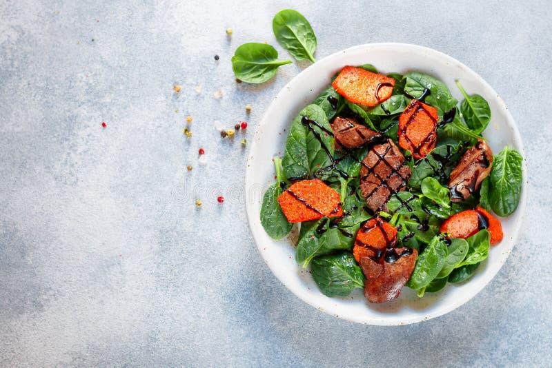 Insalata degli spinaci con il fegato di pollo e la zucca al forno con le spezie e balsamico caldi fotografia stock