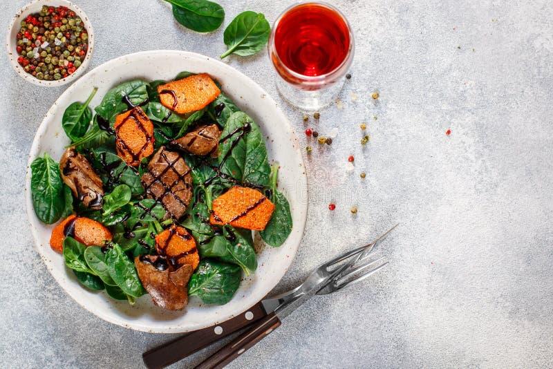 Insalata degli spinaci con il fegato di pollo e la zucca al forno con le spezie e balsamico caldi fotografia stock libera da diritti