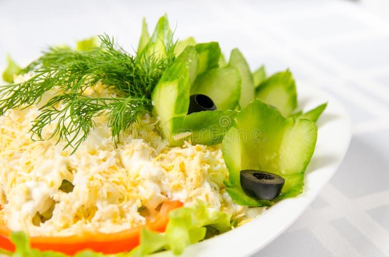 Insalata dei frutti di mare - calamaro, bastoni del granchio, cetrioli, uova, maionese, formaggio, lattuga, pomodoro, olive e ver immagini stock
