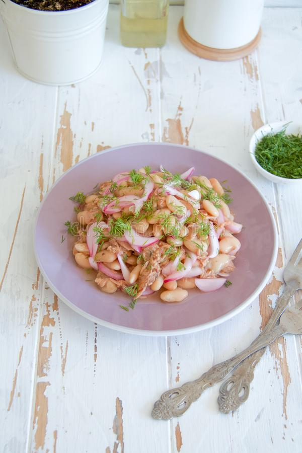 Insalata del fagiolo bianco, del tonno e della cipolla su un piatto porpora fotografie stock libere da diritti