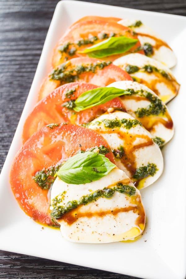 Insalata del formaggio della mozzarella e del pomodoro in piatto bianco fotografie stock libere da diritti