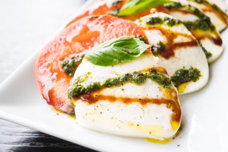 Insalata del formaggio della mozzarella e del pomodoro in piatto bianco fotografia stock