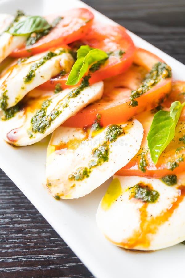 Insalata del formaggio della mozzarella e del pomodoro in piatto bianco immagini stock