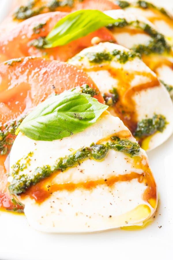 Insalata del formaggio della mozzarella e del pomodoro in piatto bianco immagine stock