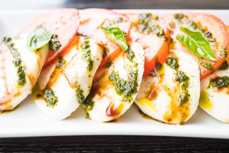 Insalata del formaggio della mozzarella e del pomodoro in piatto bianco fotografia stock libera da diritti