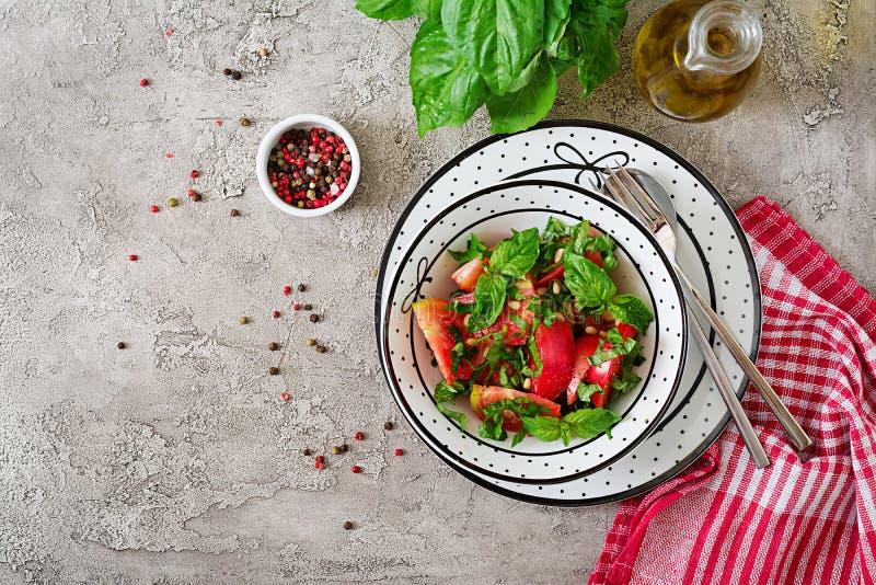 Insalata del pomodoro con basilico e pinoli in ciotola - aperitivo vegetariano sano dell'alimento biologico di dieta del vegano fotografia stock libera da diritti