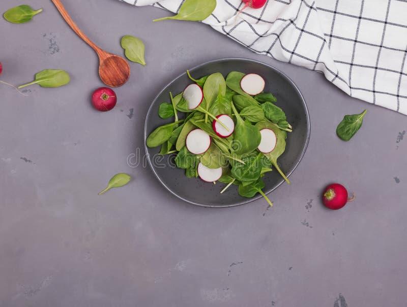 Insalata del ravanello e degli spinaci in una ciotola rustica sui precedenti di pietra grigi fotografia stock