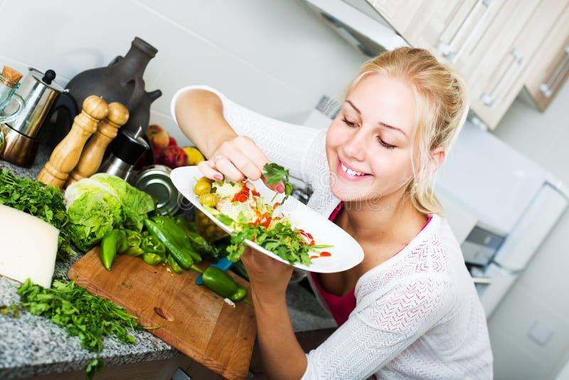 Insalata del servizio della donna sulla cucina immagine stock