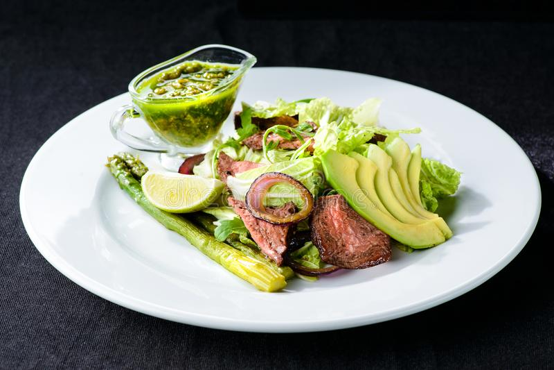 Insalata deliziosa della carne verde con bistecca succosa arrostita, avocado e fotografia stock