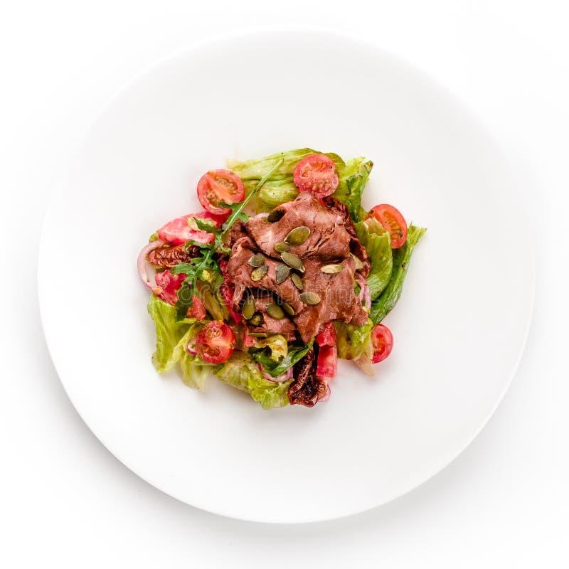 Insalata deliziosa della carne verde con bistecca succosa arrostita, il pomodoro e la salsa verde in un piatto bianco isolato su  fotografie stock