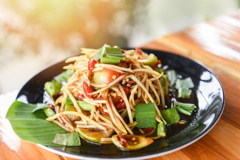 Insalata della papaia servita sul tavolo da pranzo - alimento tailandese piccante dell'insalata verde della papaia sul piatto con fotografie stock