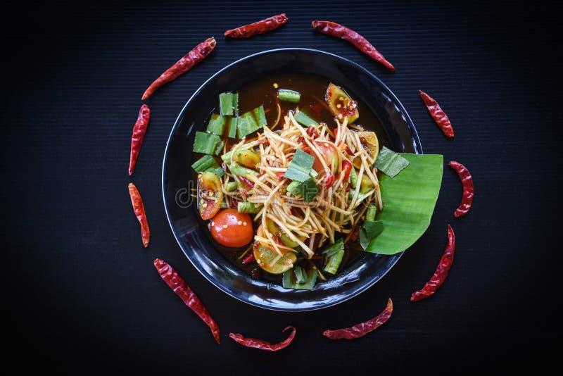 Insalata della papaia servita sull'alimento tailandese piccante insalata verde della papaia/del fondo nero sul piatto con le erbe fotografie stock libere da diritti