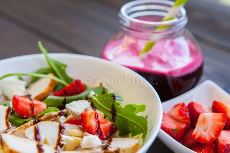 Insalata delle fragole con i pinoli, la rucola ed il pollo Succo fresco della barbabietola Alimento di forma fisica e sano immagine stock libera da diritti