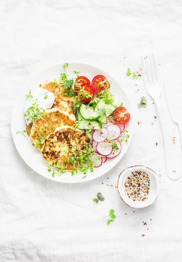 Insalata delle frittelle e degli ortaggi freschi dello zucchini di ricotta Cetrioli, pomodori ciliegia, ravanelli, micro verdi e  immagini stock