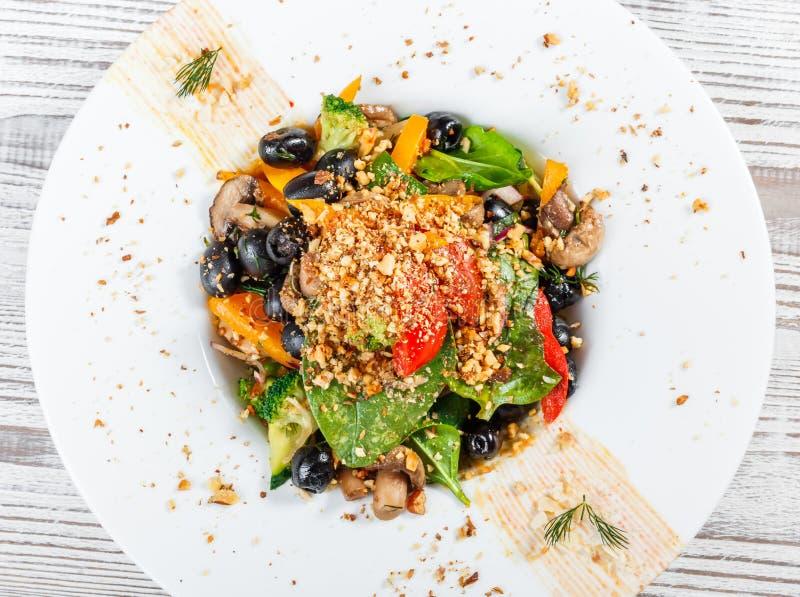 Insalata delle verdure con spinaci, i funghi, i pomodori, le cipolle, i cetrioli, i broccoli, le olive ed i dadi sul piatto immagine stock
