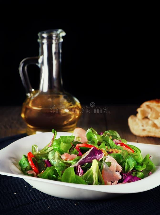 Insalata delle verdure verdi con il prosciutto di Parma su un piatto bianco con olio d'oliva rustic Fuoco selettivo La struttura  fotografia stock libera da diritti