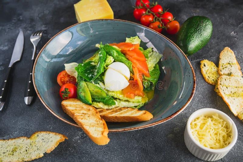Insalata di Caesar con l'uovo, il salmone, l'avocado, i pomodori ciliegia ed il pane tostato arrostito, fine sulla vista Alimento fotografie stock libere da diritti
