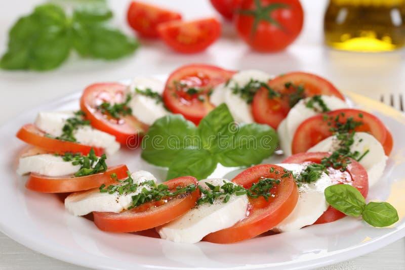 Insalata di Caprese con i pomodori ed il formaggio della mozzarella sul piatto fotografia stock libera da diritti