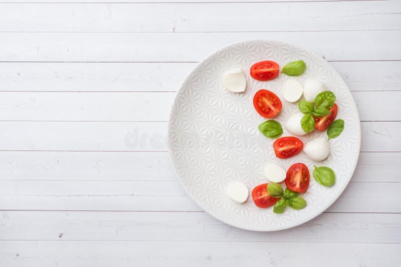 Insalata di Caprese dei pomodori, del formaggio della mozzarella e del basilico su un piatto bianco Cucina italiana Copi lo spazi immagine stock libera da diritti