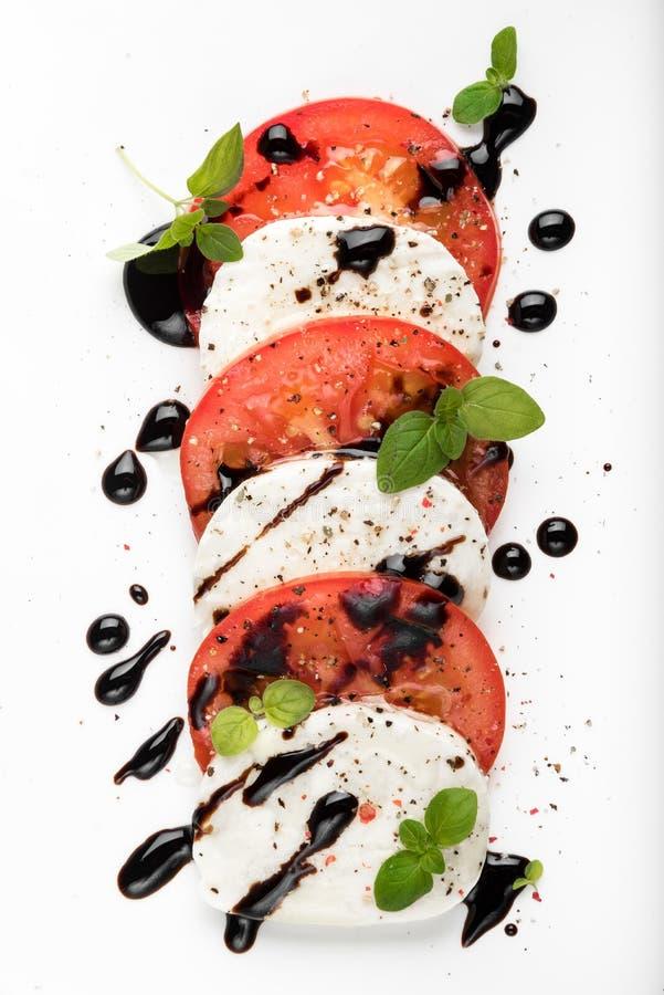 Insalata di Caprese dell'italiano con il pepe nero dell'origano del pomodoro della mozzarella e l'aceto balsamico sul piatto bian fotografie stock