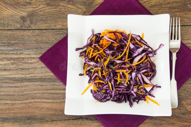 Insalata di cavolo rosso e delle carote sul piatto bianco fotografia stock libera da diritti