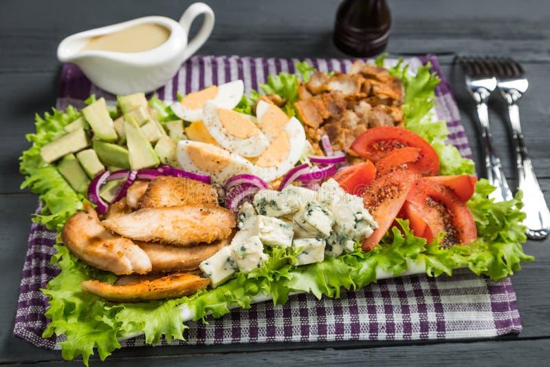 Insalata di Cobb con pollo fritto, l'avocado, le uova ed i pomodori immagine stock