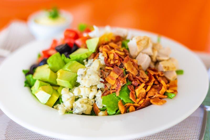 Insalata di Cobb sul piatto bianco, con bacon, formaggio blu, pollo arrostito, pomodori ed avocado tagliati cubati, olive e lectt fotografia stock libera da diritti