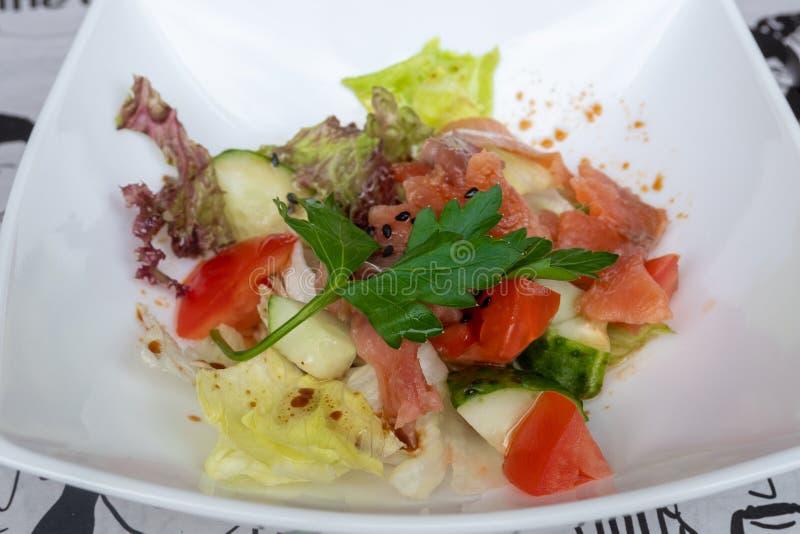 Insalata di color salmone salata con i pomodori ed i cetrioli con la salsa di soia fotografia stock