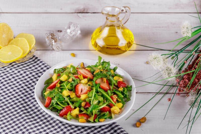 Insalata di fragole con arugula, mango e pistacchi con limone e olio di oliva fotografie stock