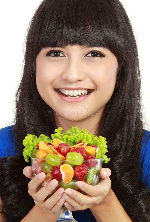 Insalata di frutta della holding della signora abbastanza giovane fotografia stock
