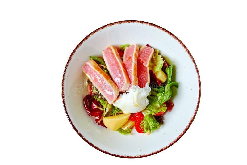 Insalata di Nicoise del tonno, della patata, del preparato dell'insalata e dell'uovo affogato fritti rari in piatto bianco, isola fotografie stock libere da diritti