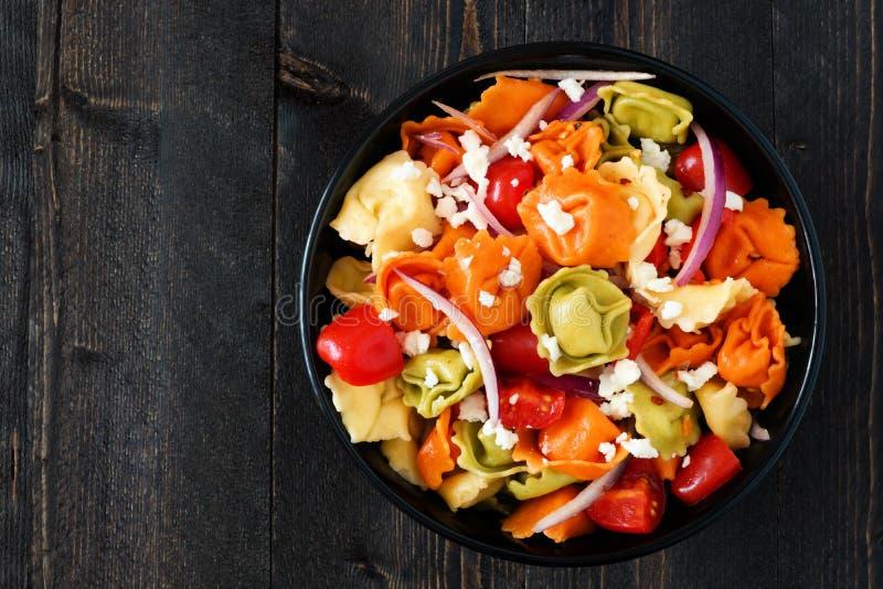 Insalata di pasta multicolore dei tortellini, vista sopraelevata su legno scuro immagini stock