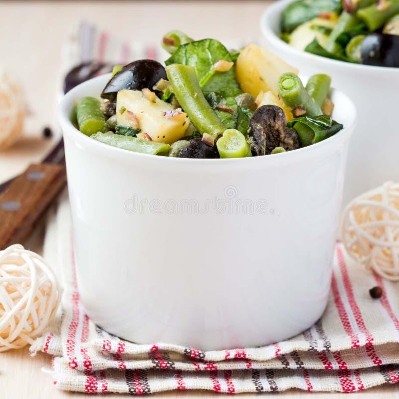 Insalata di patata con i fagiolini, olive, capperi, cipolle, deliziose fotografie stock libere da diritti