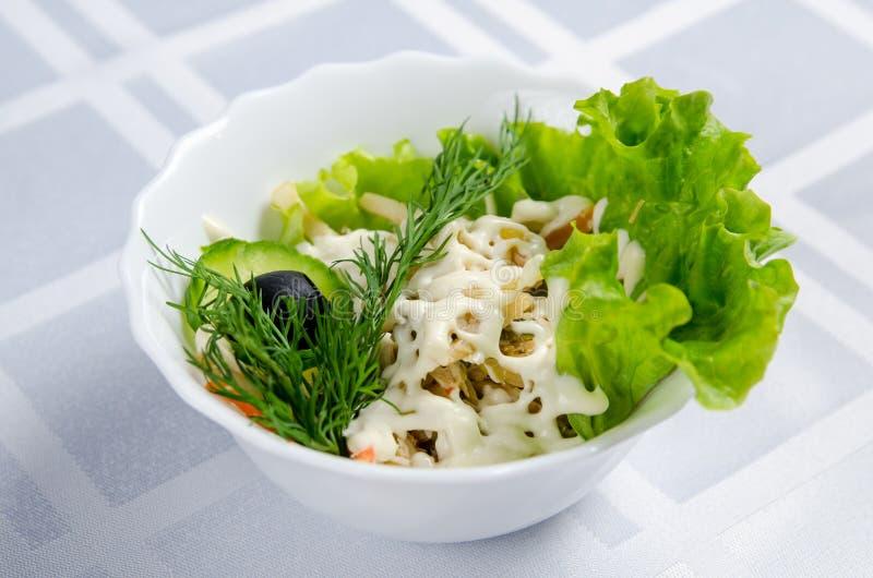 Insalata di pollo bollita con il calamaro, i cetrioli marinati, la maionese, le carote, la lattuga, i verdi e l'oliva in piatto b fotografia stock