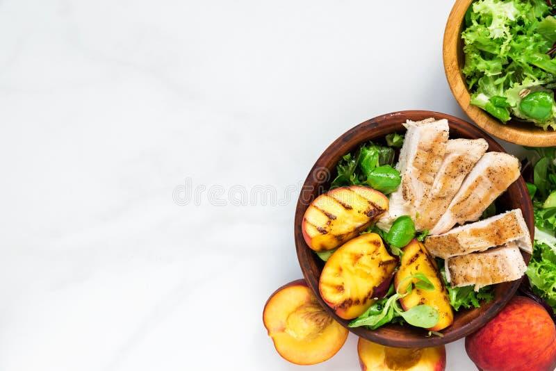 Insalata di pollo con la pesca arrostita ed insalata mista in una ciotola Alimento sano Vista superiore fotografia stock libera da diritti
