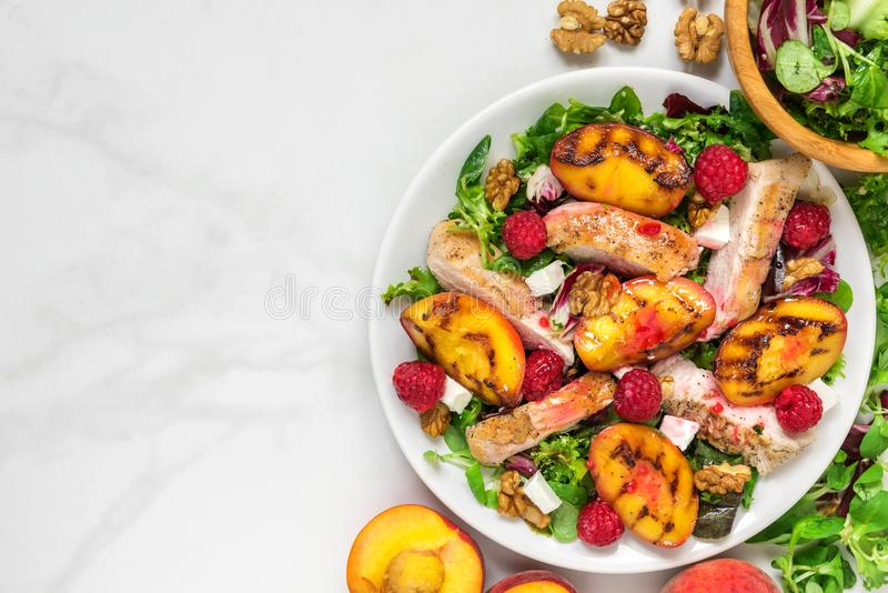Insalata di pollo con la pesca arrostita, insalata mista, feta, lamponi e noci in un piatto Alimento sano Vista superiore fotografia stock