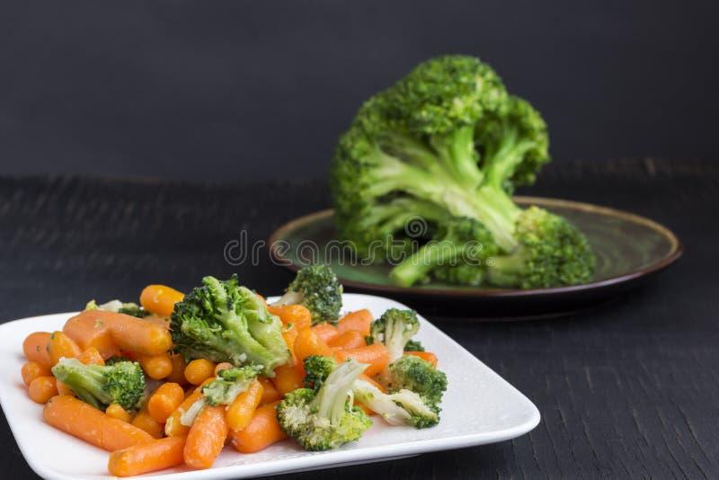 Insalata di verdure: broccoli e carote in un piatto bianco su un fondo nero fotografie stock
