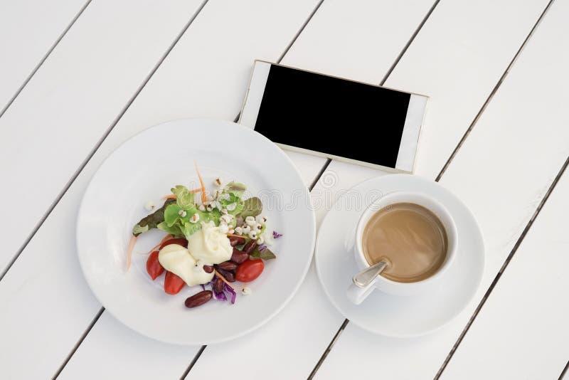 Insalata di verdure, caffè istantaneo in tazza e smartphone sullo scrittorio di legno bianco immagine stock libera da diritti