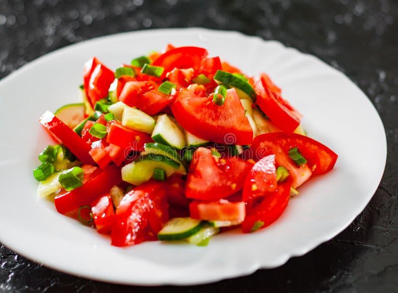 Insalata di verdure con il pomodoro, il cetriolo e la cipolla verde in piatto bianco su fondo nero fotografia stock libera da diritti