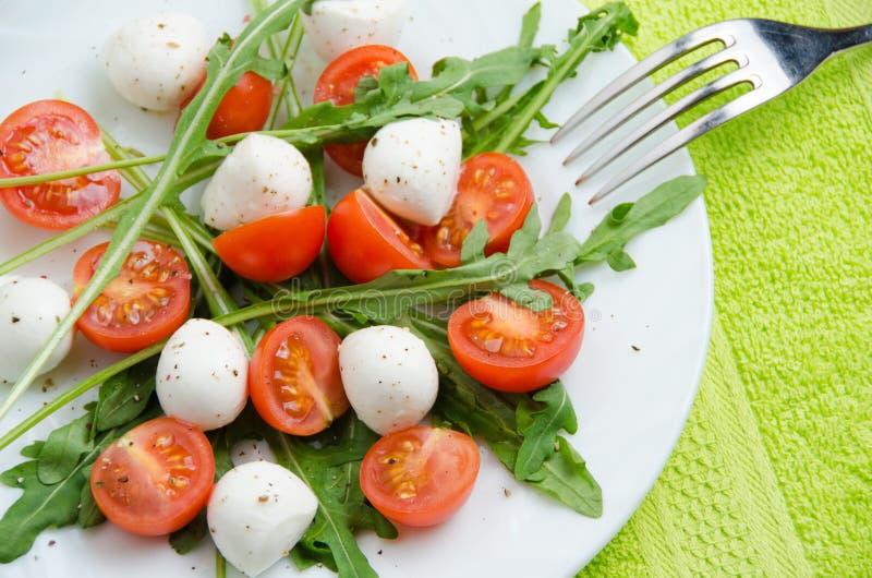 Insalata di verdure della rucola, dei pomodori ciliegia e della mozzarella immagini stock