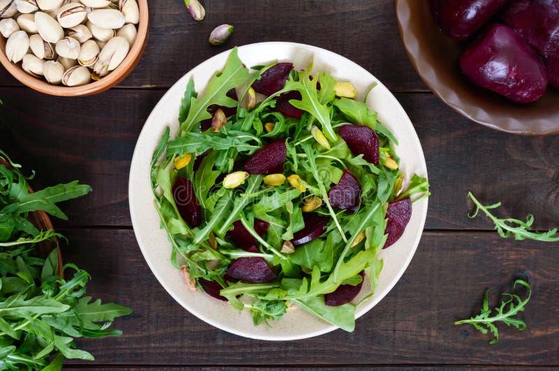 Insalata di verdure della vitamina del vegano dalle barbabietole, dalla rucola e dai pistacchi fotografie stock libere da diritti