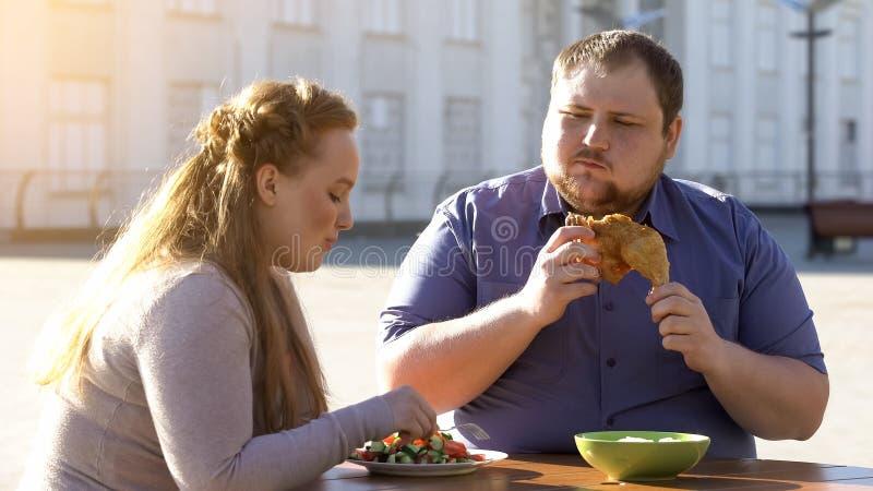 Insalata di verdure di giovane cibo femminile, uomo che mastica pollo fritto, scelta di dieta fotografie stock