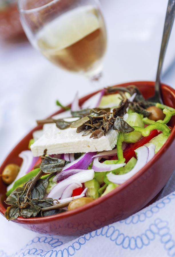 Insalata di verdure in una ciotola dell'argilla ed in un vetro di vino bianco fotografia stock libera da diritti