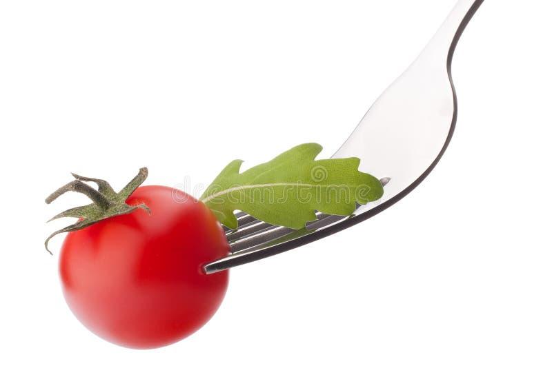 Insalata e pomodoro ciliegia freschi di rucola sulla forcella isolata su bianco immagine stock libera da diritti
