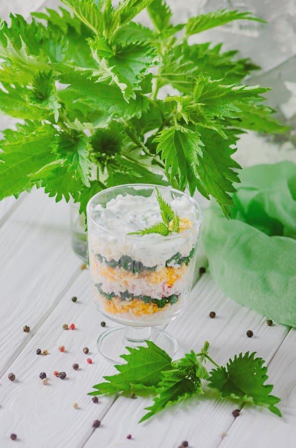 Insalata esotica con le ortiche e le uova in un rivestito di vetro negli strati fotografie stock
